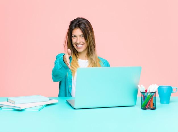 Junge hübsche frau, die mit einem lächelnden gruß des laptops sie arbeitet und einen händedruck anbietet, um ein erfolgreiches abkommenzusammenarbeitskonzept zu schließen