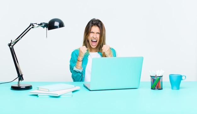 Junge hübsche frau, die mit einem laptop aggressiv schreit mit dem gestörten, frustrierten, verärgerten blick und den festen fäusten arbeitet und fühlt sich wütend