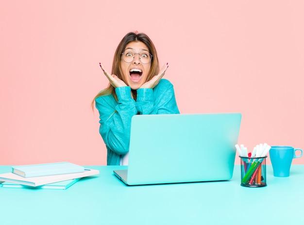 Junge hübsche frau, die mit einem laptop arbeitet, der wegen einer unerwarteten überraschung entsetzt und aufgeregt, lachend, überrascht und glücklich sich fühlt