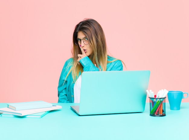 Junge hübsche frau, die mit einem laptop bittet um ruhe und frieden, gestikuliert mit dem finger vor mund, sagt shh oder hält ein geheimnis