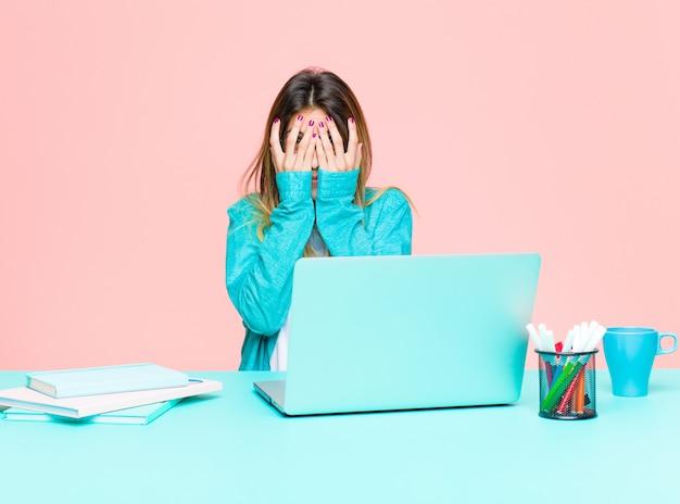 Junge hübsche frau, die mit einem laptop glaubt erschrocken oder verlegen arbeitet, späht oder mit den augen ausspioniert, die mit den händen halb bedeckt sind