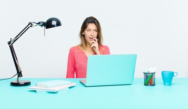 Junge hübsche frau, die mit einem laptop mit dem überraschten, nervösen, besorgten oder erschrockenen blick, schauend zur seite in richtung zum kopienraum arbeitet