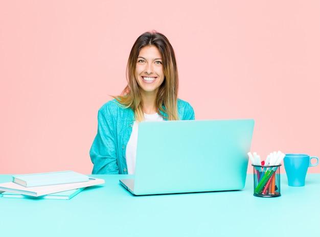 Junge hübsche frau, die mit einem laptop positiv und sicher lächelt und zufrieden, freundlich und glücklich schaut arbeitet
