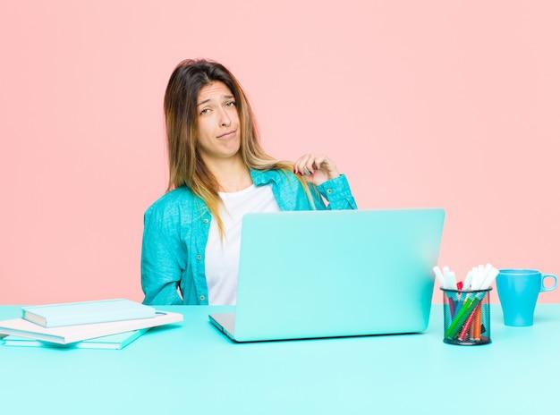 Junge hübsche frau, die mit einem laptop schaut arrogant, erfolgreich, positiv und stolz arbeitet und zeigt auf selbst