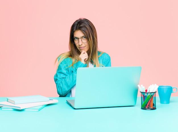 Junge hübsche frau, die mit einem laptop schaut ernst, verwirrt, unsicher und durchdacht arbeitet