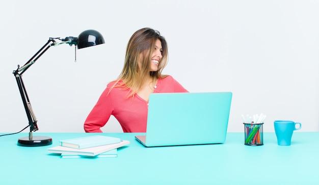 Junge hübsche frau, die mit einem laptop schaut glücklich, nett und überzeugt arbeitet, stolz lächelt und schaut, um mit beiden händen auf hüften mit seiten zu versehen