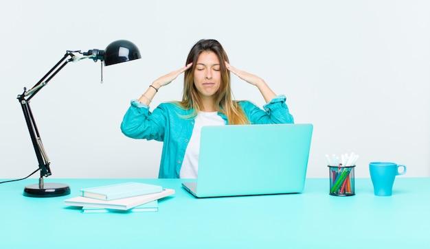 Junge hübsche frau, die mit einem laptop schaut konzentriert, durchdacht und angespornt arbeitet, mit den händen auf stirn gedanklich löst und sich vorstellt