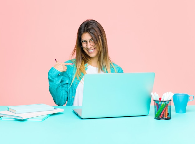 Junge hübsche frau, die mit einem laptop schaut stolz, überzeugt und glücklich arbeitet, auf selbst lächelt und zeigt oder nummer eins-zeichen macht