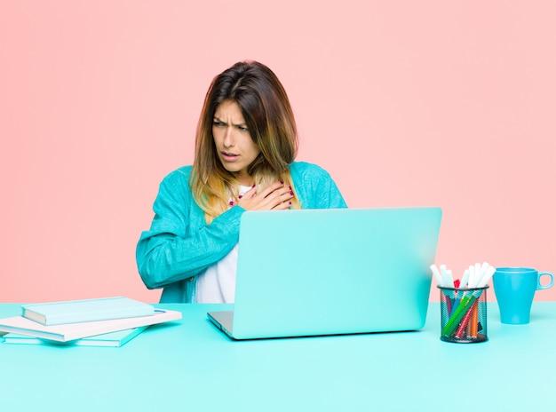 Junge hübsche frau, die mit einem laptop schaut traurig, verletzt und mit gebrochenem herzen arbeitet, beide hände nah an innerem hält, schreit und niedergedrückt sich fühlt
