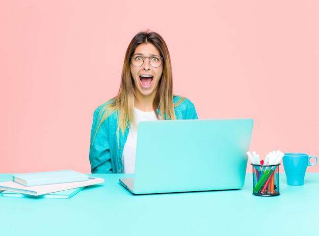 Junge hübsche frau, die mit einem laptop sich fühlt erschrocken und entsetzt, wenn der breite mund in der überraschung geöffnet ist