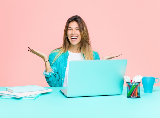Junge hübsche frau, die mit einem laptop sich fühlt glücklich aufgeregt überrascht oder entsetzt lächelnd und an etwas unglaublich überrascht arbeitet