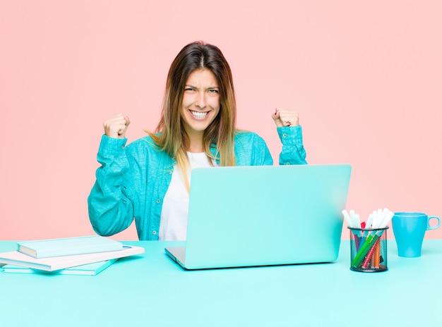 Junge hübsche frau, die mit einem laptop sich fühlt glücklich, überrascht und stolz, erfolg mit einem großen lächeln schreit und feiert
