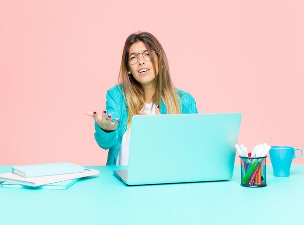 Junge hübsche frau, die mit einem laptop sich fühlt glücklich und in der liebe arbeitet