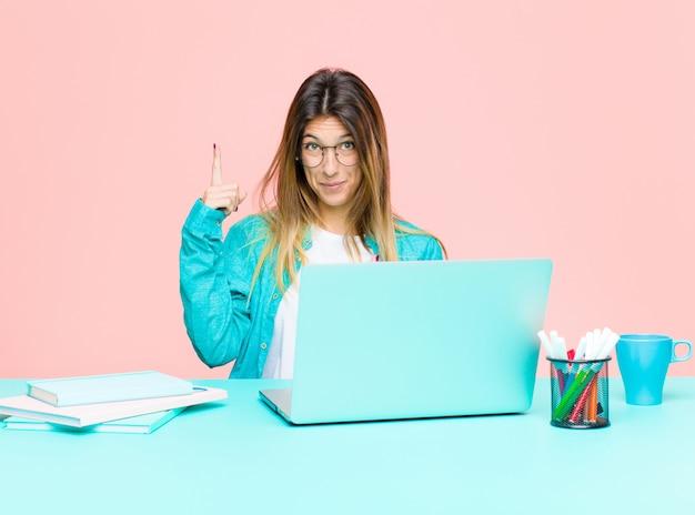 Junge hübsche frau, die mit einem laptop sich fühlt stolz und überrascht arbeitet und sicher auf selbst zeigt und wie erfolgreiches nummer eins glaubt