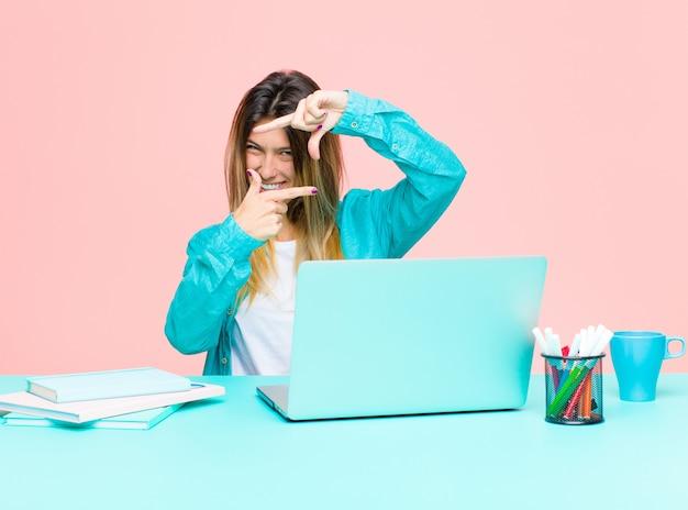 Junge hübsche frau, die mit einem laptop sich glücklich, freundlich und positiv fühlt, ein porträt oder einen fotorahmen mit den händen lächelt und macht
