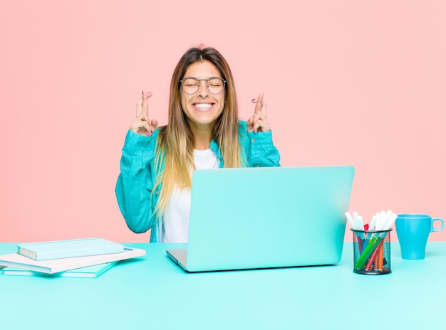 Junge hübsche frau, die mit einem laptop sich nervös und hoffnungsvoll fühlt, finger kreuzt, für gutes glück betet und hofft