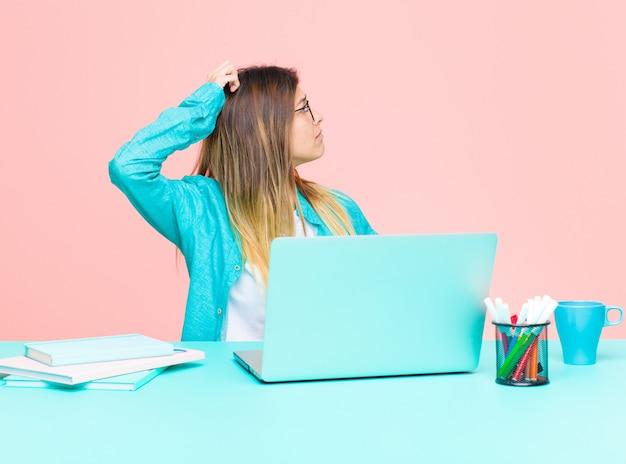Junge hübsche frau, die mit einem laptop sich verwirrt fühlt oder voll oder zweifeln und fragen, wundernd, mit den händen auf hüften, hintere ansicht arbeitet