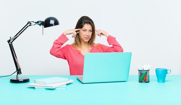 Junge hübsche frau, die mit einem laptop sich verwirrt fühlt oder zweifelt, sich auf eine idee konzentriert, stark denkt und schaut, um raum auf seite zu kopieren