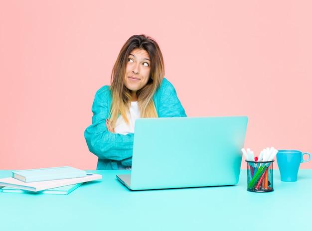 Junge hübsche frau, die mit einem laptop zuckt, sich verwirrt und unsicher fühlt und mit den gekreuzten armen und verwirrtem blick zweifelt