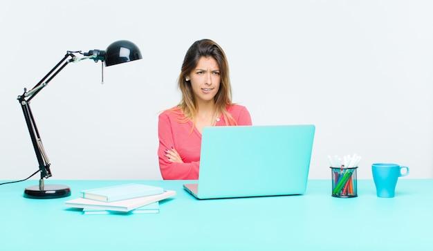 Junge hübsche frau, die mit einem laptop zweifelt oder denkt, lippen beißt und sich unsicher und nervös fühlt und schaut, um raum auf der seite zu kopieren