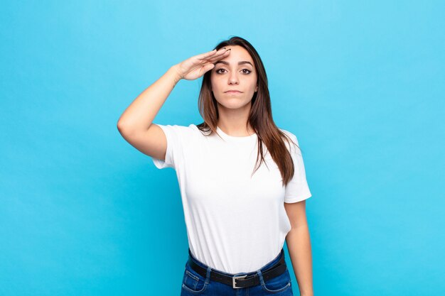 Junge hübsche frau, die mit einem militärischen gruß in einem akt der ehre und des patriotismus grüßt und respekt gegen blaue wand zeigt