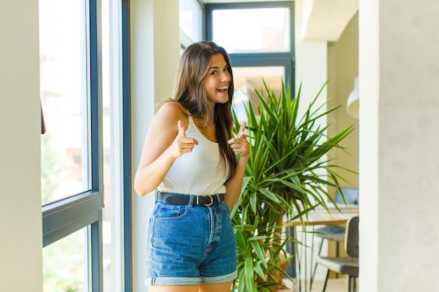 Junge hübsche frau, die mit einer positiven, erfolgreichen, glücklichen haltung lächelt, die nach vorne zeigt und waffenzeichen mit händen macht