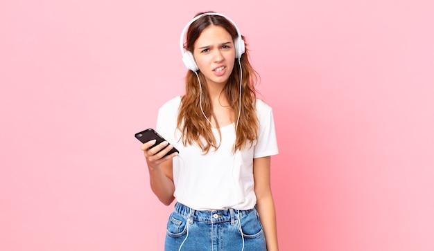 Junge hübsche frau, die mit kopfhörern und einem smartphone verwirrt und verwirrt ist
