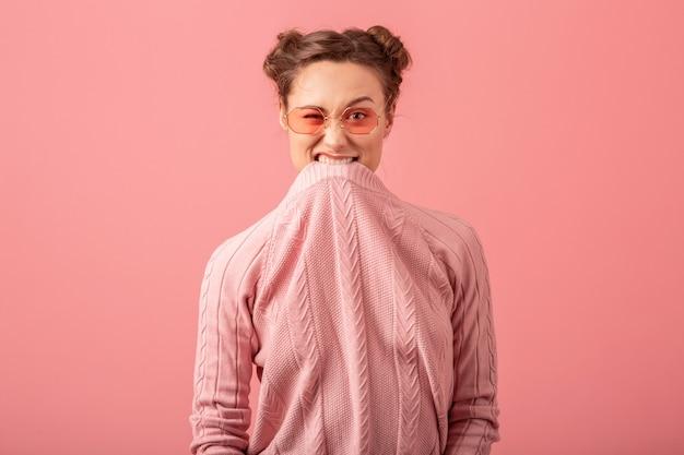 Junge hübsche frau, die mit lustigem gesichtsausdruck in rosa pullover und sonnenbrille lokalisiert auf rosa studiohintergrund täuscht Kostenlose Fotos