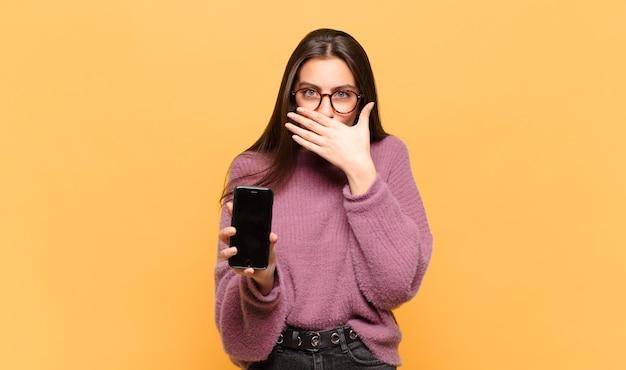 Junge hübsche frau, die mund mit händen mit einem schockierten, überraschten ausdruck bedeckt, ein geheimnis hält oder oops sagt. telefonbildschirmkonzept