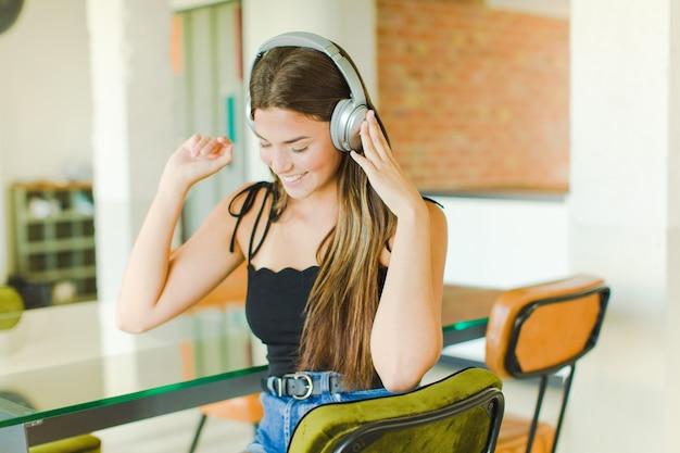 Junge hübsche frau, die musik hört und tanzt