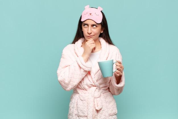 Junge hübsche frau, die nachdenkt, sich zweifelnd und verwirrt fühlt, mit verschiedenen optionen und sich fragt, welche entscheidung sie treffen soll. erwachen mit pyjama-konzept