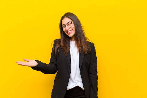 Junge hübsche frau, die nett lächelt, ein konzept im kopienraum mit palme der hand auf orange wand glücklich sich fühlt und zeigt