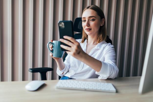 Junge hübsche frau, die online mit einem pc und einem telefon in einem desktop im büro arbeitet