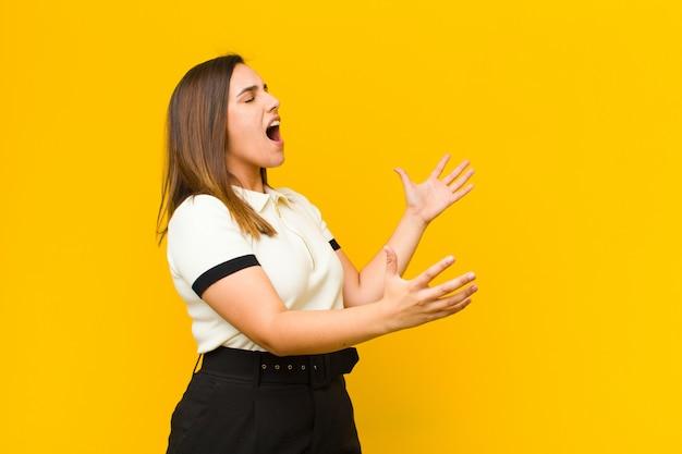 Junge hübsche frau, die oper durchführt oder bei einem konzert oder einer show singt, sich romantisch, künstlerisch und leidenschaftlich isoliert gegen orange wand fühlt