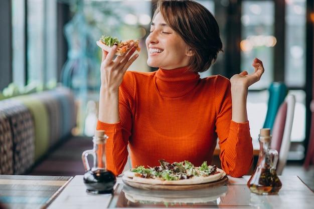 Junge hübsche frau, die pizza an der pizzabar isst