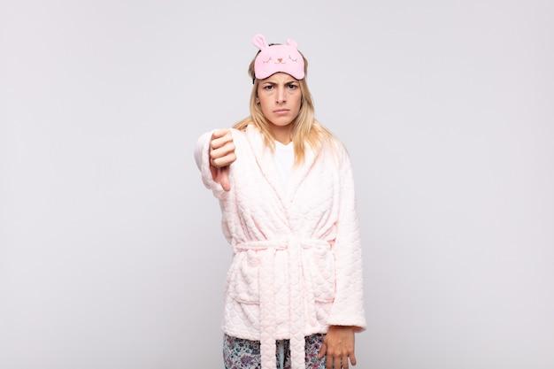 Junge hübsche frau, die pyjamas trägt, sich böse, wütend, genervt, enttäuscht oder unzufrieden fühlt und daumen mit einem ernsten blick nach unten zeigt