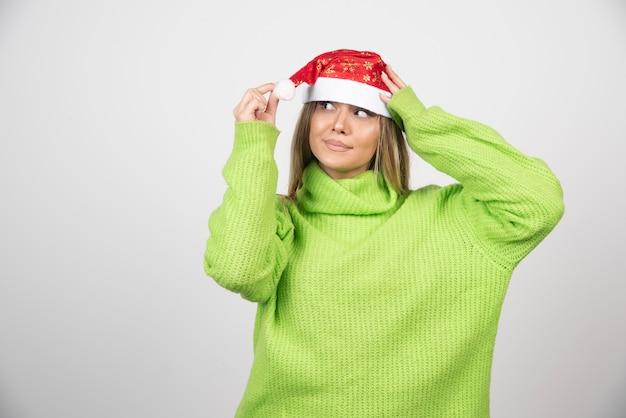 Junge hübsche frau, die roten hut des weihnachtsmanns trägt.