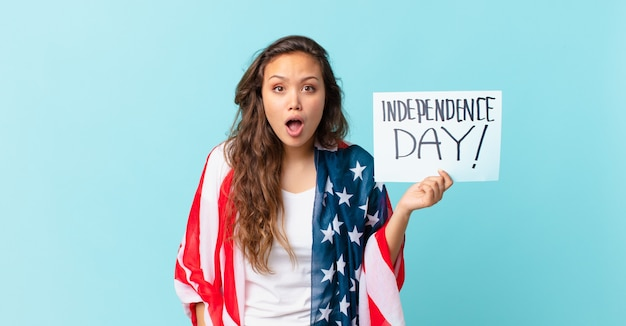 Junge hübsche frau, die sehr schockiert oder überrascht aussieht, konzept des unabhängigkeitstages