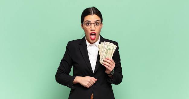 Junge hübsche frau, die sehr schockiert oder überrascht aussieht und mit offenem mund anstarrt und sagt wow. geschäfts- und banknotenkonzept