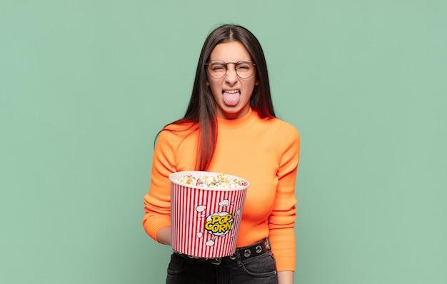 Junge hübsche frau, die sich angewidert und gereizt fühlt, die zunge herausstreckt und etwas böses und glückliches nicht mag. popcorn-konzept