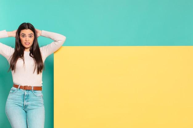 Junge hübsche frau, die sich gestresst, besorgt, ängstlich oder ängstlich fühlt, mit den händen auf dem kopf, die bei einem fehler in panik geraten. kopieren sie den speicherplatz, um ihr konzept zu platzieren