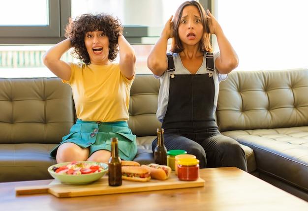 Junge hübsche frau, die sich gestresst, besorgt, ängstlich oder ängstlich fühlt, mit den händen auf dem kopf, die bei einem fehler in panik geraten