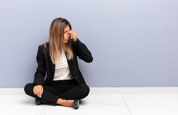 Junge hübsche frau, die sich gestresst, unglücklich und frustriert fühlt, stirn berührt und migräne des geschäftskonzepts der starken kopfschmerzen leidet