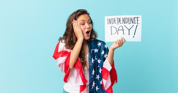 Junge hübsche frau, die sich glücklich, aufgeregt und überrascht fühlt, konzept des unabhängigkeitstages