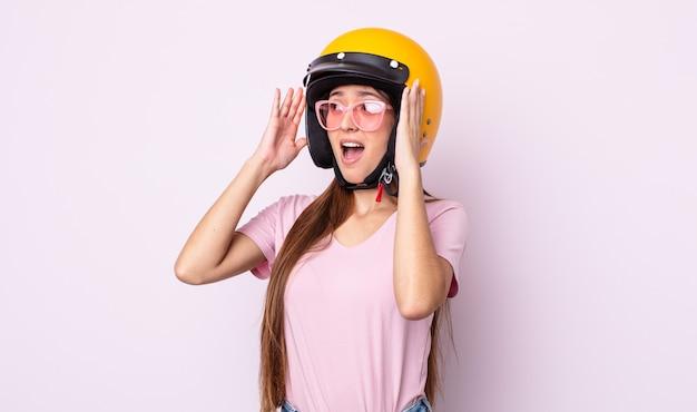 Junge hübsche frau, die sich glücklich, aufgeregt und überrascht fühlt. motorradfahrer und helm