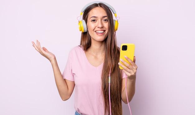 Junge hübsche frau, die sich glücklich fühlt, überrascht, eine lösung oder idee zu verwirklichen. kopfhörer und smartphone