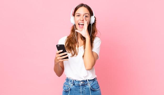 Junge hübsche frau, die sich glücklich fühlt und mit den händen neben dem mund mit kopfhörern und einem smartphone einen großen schrei ausspricht