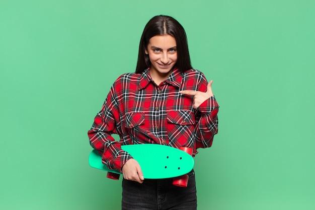Junge hübsche frau, die sich glücklich, überrascht und stolz fühlt und mit einem aufgeregten, erstaunten blick auf sich selbst zeigt. skateboard-konzept