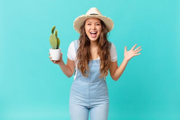 Junge hübsche frau, die sich glücklich und erstaunt über etwas unglaubliches fühlt und einen kaktus hält
