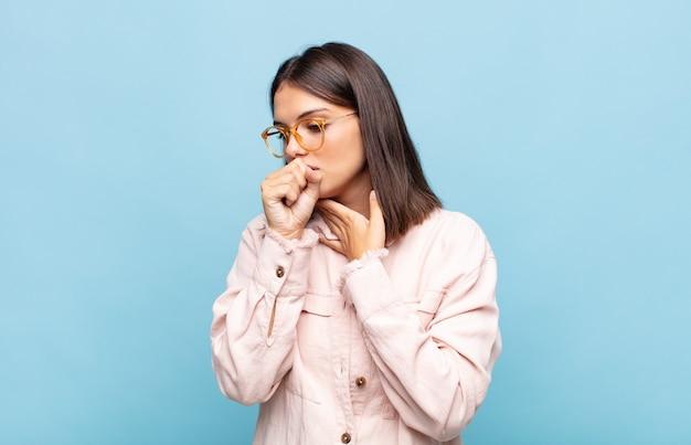 Junge hübsche frau, die sich mit halsschmerzen und grippesymptomen krank fühlt und mit bedecktem mund hustet